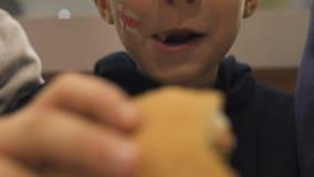 吃在便当咖啡馆,在童年的不健康的营养的小男孩汉堡包 股票视频