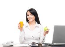 吃在办公室的一名愉快的女实业家 免版税库存图片