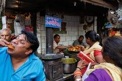 吃在印地安市场上的人们 免版税库存图片