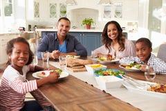 吃在厨房用桌上的父母和孩子看对照相机 免版税图库摄影