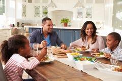 吃在厨房用桌上的父母和他们的两个孩子 免版税库存照片