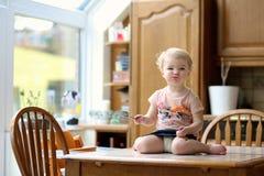 吃在厨房里的滑稽的小女孩 库存图片