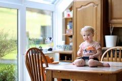 吃在厨房里的滑稽的小女孩 免版税库存图片