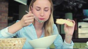 吃在咖啡馆的可爱的妇女鲜美汤在城市 股票录像