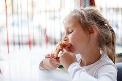 吃在咖啡馆的小女孩一个薄饼 免版税图库摄影