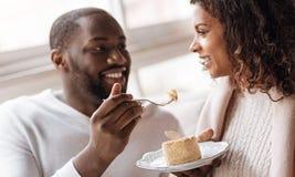 吃在咖啡馆的快乐的非裔美国人的夫妇点心 图库摄影