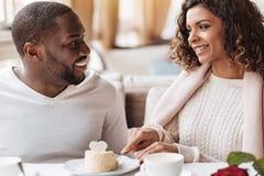 吃在咖啡馆的快乐的非裔美国人的夫妇蛋糕 图库摄影