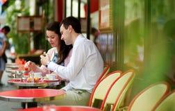 吃在咖啡馆的愉快的夫妇蛋白杏仁饼干 免版税图库摄影
