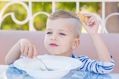 吃在咖啡馆的愉快的小男孩汤 库存照片