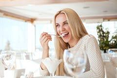 吃在咖啡馆的美丽的少妇冰淇凌 库存照片