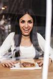 吃在咖啡馆的美丽的微笑的少妇三明治 咖啡馆风 免版税库存图片