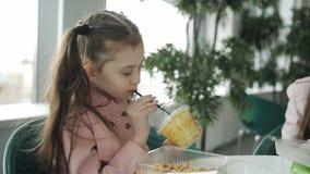 吃在咖啡馆面条和饮用的红萝卜汁的女孩从秸杆 女孩喝从塑料杯的汁液在a 股票录像