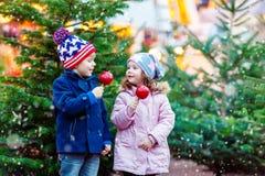 吃在圣诞节市场上的两个小孩被结晶的苹果 库存图片