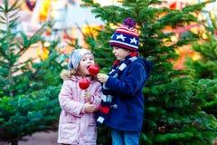 吃在圣诞节市场上的两个小孩被结晶的苹果 免版税库存照片
