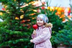 吃在圣诞节市场上的小孩女孩被结晶的苹果 免版税库存图片