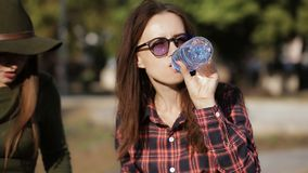 吃在城市街道三明治的两个朋友午餐 女孩喝从瓶的水 影视素材