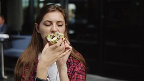 吃在城市街道咖啡馆的可爱的少妇新鲜的可口三明治 股票视频
