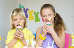 吃在复活节场面的愉快的孩子杯形蛋糕 免版税库存图片