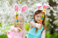 吃在复活节的两个可爱的妹五颜六色的胶糖果 免版税库存图片