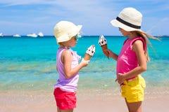 吃在夏天海滩背景的愉快的小女孩冰淇凌 人们、孩子、朋友和友谊概念 免版税库存图片