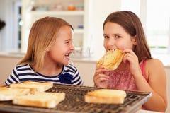 吃在多士的两个女孩乳酪在厨房里 免版税库存照片