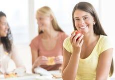 吃在大学餐厅的少年学生苹果计算机 库存图片