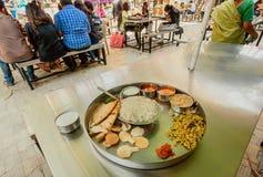 吃在室外咖啡馆的学生印地安vegeterian食物thali 免版税库存图片
