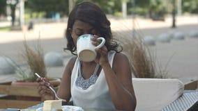 吃在室外咖啡馆的年轻黑人妇女画象  库存图片