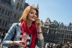吃在布鲁塞尔大广场的妇女巧克力在布鲁塞尔 免版税库存照片