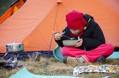 吃在帐篷旁边的一个小女孩 免版税库存照片