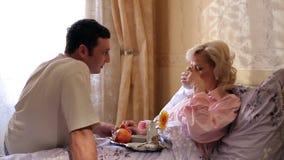 吃在床上的快乐的白肤金发的妇女早餐 股票录像