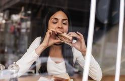 吃在快餐咖啡馆的少妇一个三明治 咖啡馆窗口 图库摄影