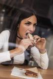 吃在快餐咖啡馆的少妇一个三明治 咖啡馆窗口 免版税库存图片