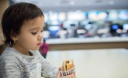 吃在快餐的逗人喜爱的女孩一个汉堡包 免版税图库摄影
