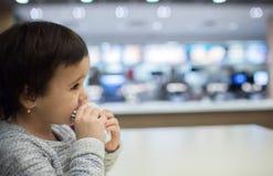 吃在快餐的逗人喜爱的女孩一个汉堡包 免版税库存图片