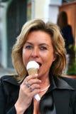 吃在意大利冰淇凌店前面的可爱的妇女冰淇凌, Gelateria 免版税库存照片