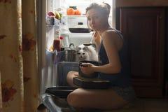 吃在晚上的女孩和她的蓬松猫 免版税库存照片