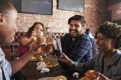 吃在有屏幕的娱乐酒吧的朋友在背景中 库存图片
