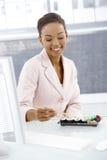 吃在服务台的微笑的女实业家 免版税库存图片
