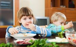 吃在木桌上的孩子 图库摄影