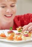 吃在板材的妇女开胃菜 库存照片
