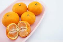 吃在桃红色盘子的桔子 免版税库存照片