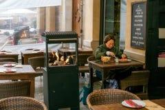 吃在桌上的妇女在街道餐馆 免版税库存图片