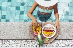 吃在水池的女孩异乎寻常的果子 免版税库存照片