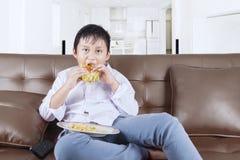 吃在沙发的男孩一个乳酪汉堡 免版税库存照片