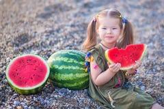 吃在海滩的女孩西瓜,享受接近海洋的夏令时好天气 免版税库存照片
