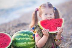吃在海滩的女孩西瓜,享受接近海洋的夏令时好天气 库存图片
