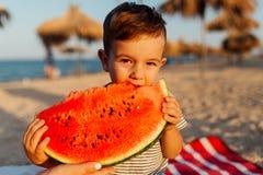 吃在海滩的小男孩西瓜 免版税库存照片