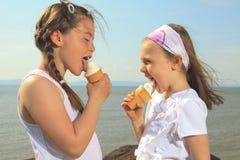 吃在海洋前面的姐妹ici奶油 库存图片
