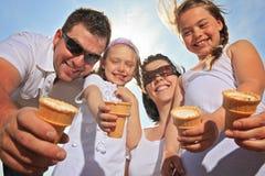 吃在海洋前面的家庭ici奶油 免版税库存照片